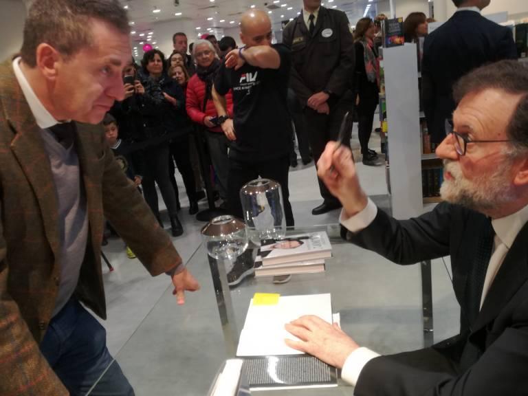El autor del artículo escucha al expresidente durante la firma el libro.